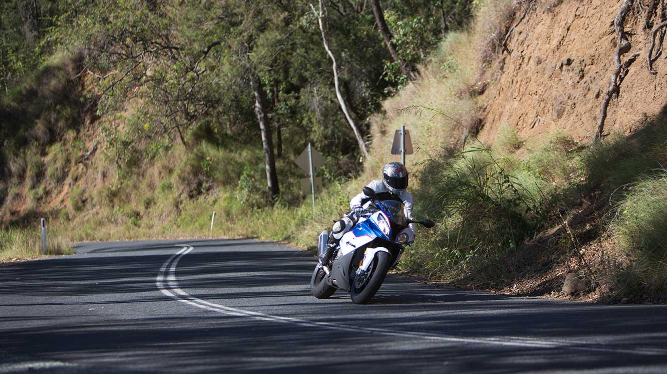 View of BMW motorcycle rider leaning over and taking a corner