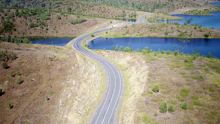 Ariel shot of long winding country road passing over a body of water