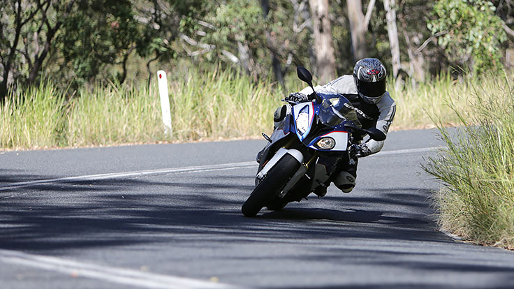 View of rider on BMW motorcycle leaning into corner