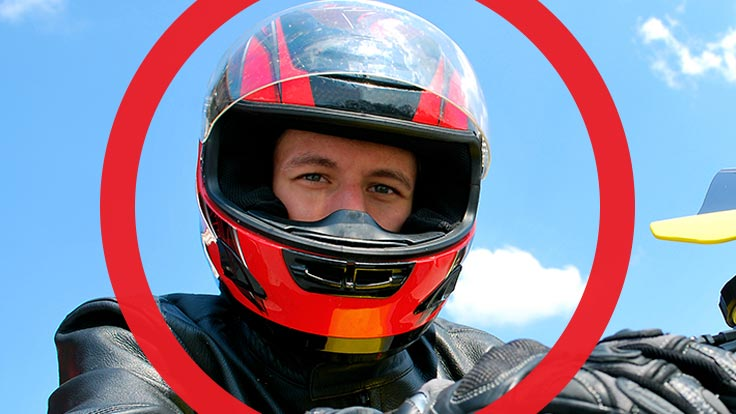 Portrait of man wearing motorcycle helmet with thick red circle framing his face