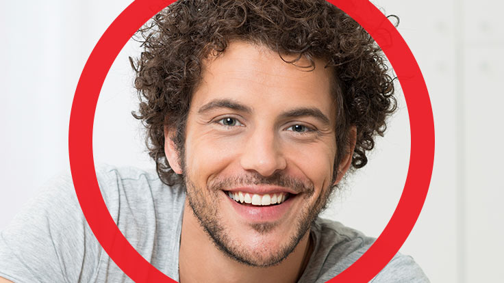 Portrait of young man with black curly hair with large smile on his face with thick red circle framing him
