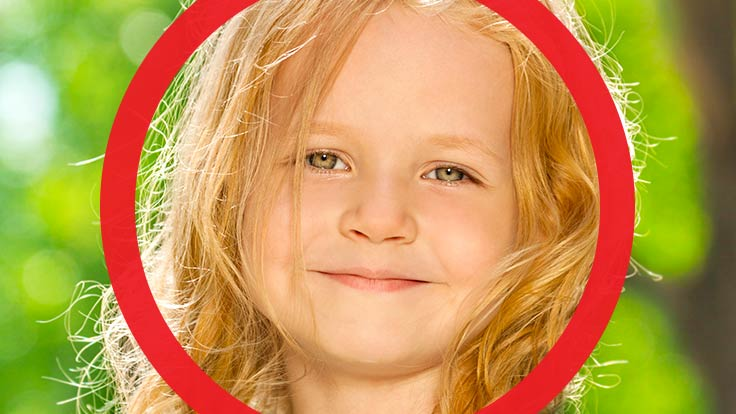 Young girl smiling and looking into camera with thick red circle framing her face