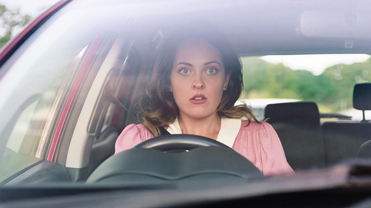 Picture of woman through car windscreen with shocked look on her face