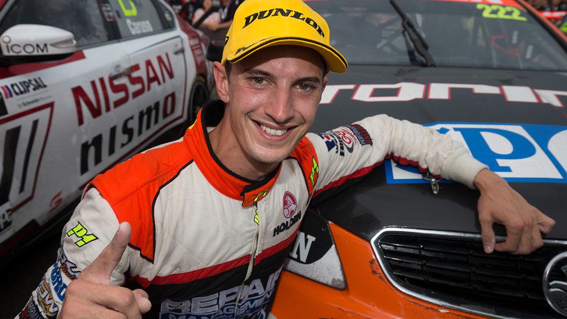 Nick Percat crouching in front of his car smiling to camera