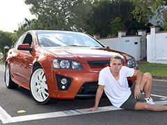 Young man sits seductively in front of a car