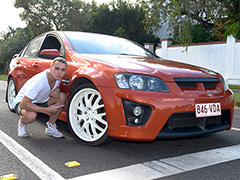 Young man crouches and points to the wheels of his car