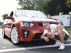 Young man crouching down in front of a car