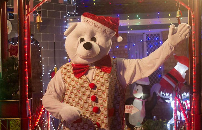 Person in polar bear costume with bow tie, vest and Santa hat