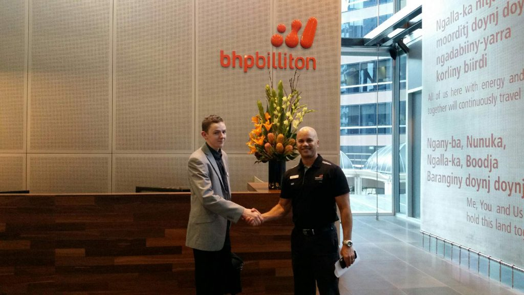 Jed shaking hands with Training Manager Bernie Reviere at the BHP office