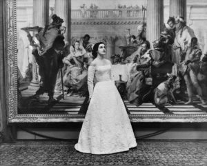 2009/43/1-5/17/12 Negative, black and white, 4x5 inch format, model Catherine Patchell (nee Perkins) wearing Henry Haskin Gown of the Year, photographed in front of the 'Banquet of Cleopatra' painting, photograph by Bruno Benini, National Gallery of Victoria, Australia. Edited version of scan 00239324