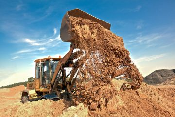 Wheel loader machine unloading soil at construction site