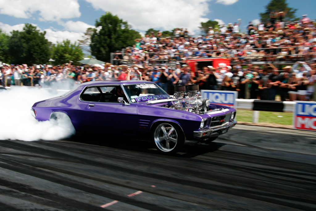A purple muscle car doing a burnout at Summernats