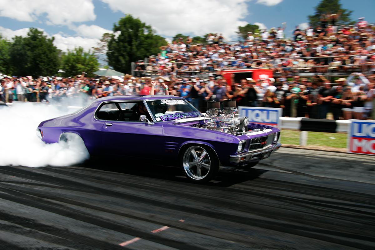 A purple muscle car doing a burnout at Summernats