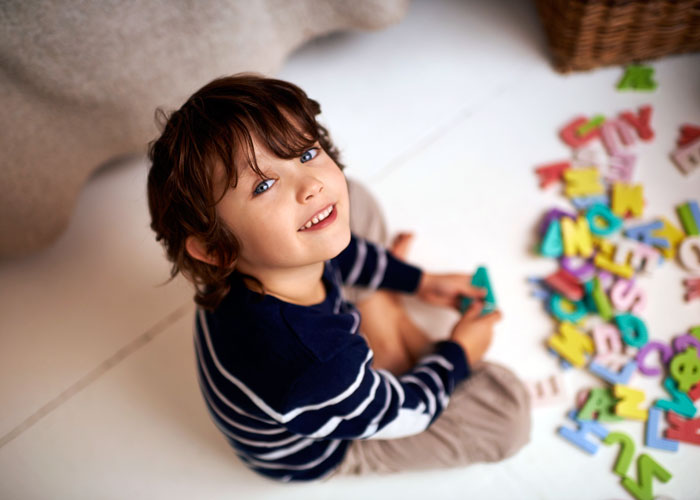 A boy looks up at the camera and smiles as he sits on a white tile floor playing with the letters of the alphabet.