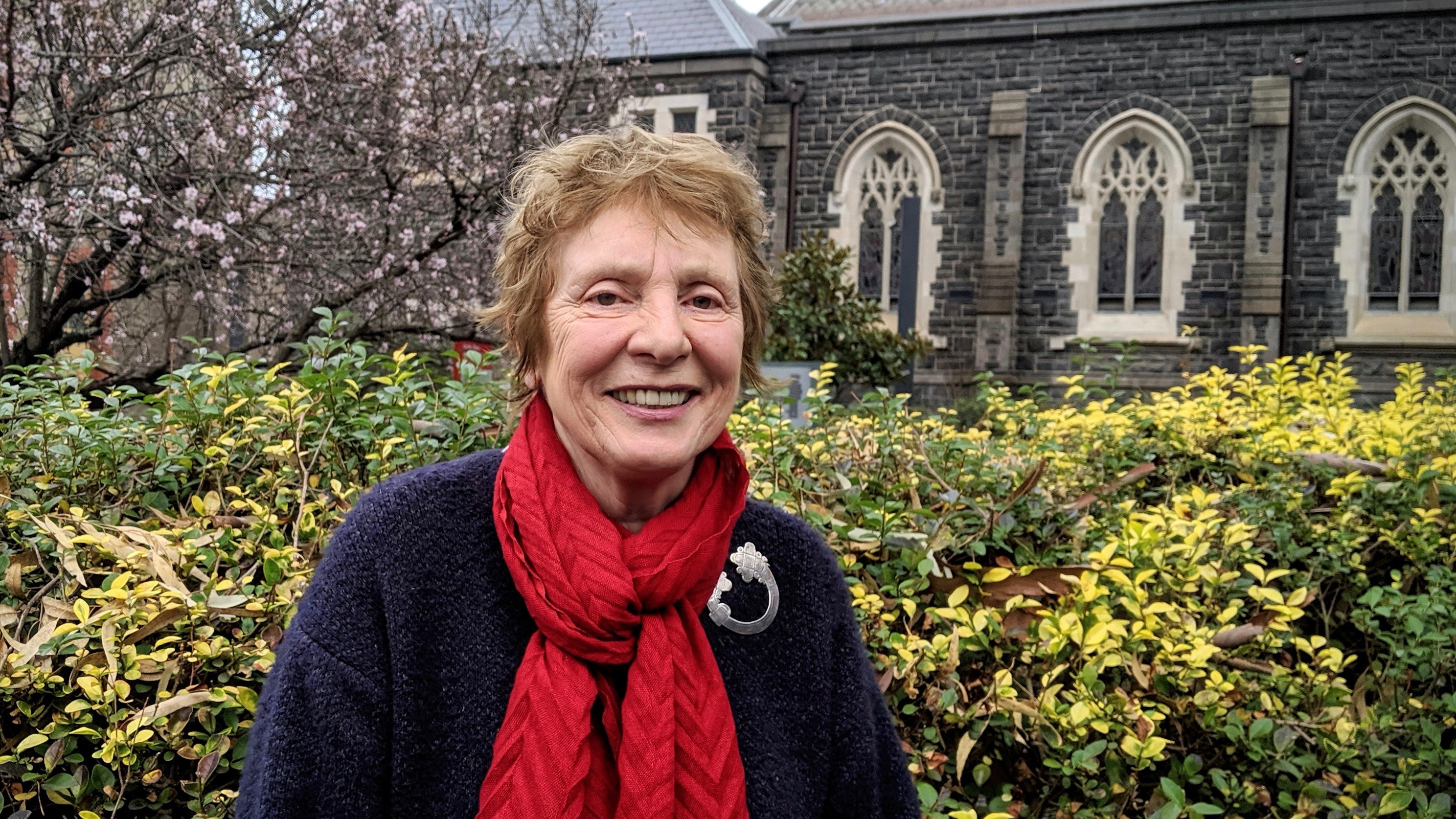 A picture of Mary Rylli Clark standing in front of the Good Shepherd Chapel at the Abbotsford Convent
