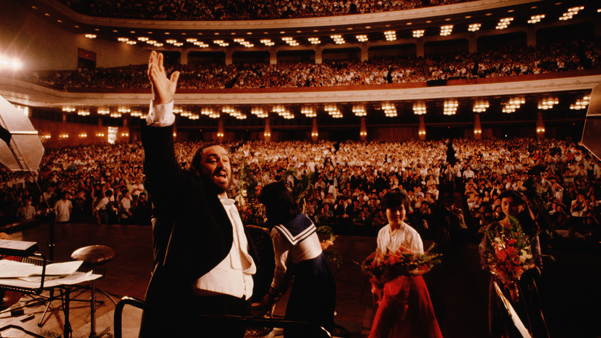 Opera singer Pavarotti waves his hand in front of his audience in an auditorium.