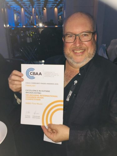 3MBS Program Manager, Adrian McEniery holds a certificate from CBAA recognising the station's nomination.