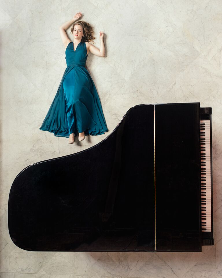 A woman in a blue dress lies against the wall above a grand piano.