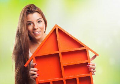 portrait of a pretty woman holding a house design