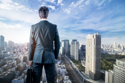 Businessman Looking Down A Modern City. Business Prospect Concept