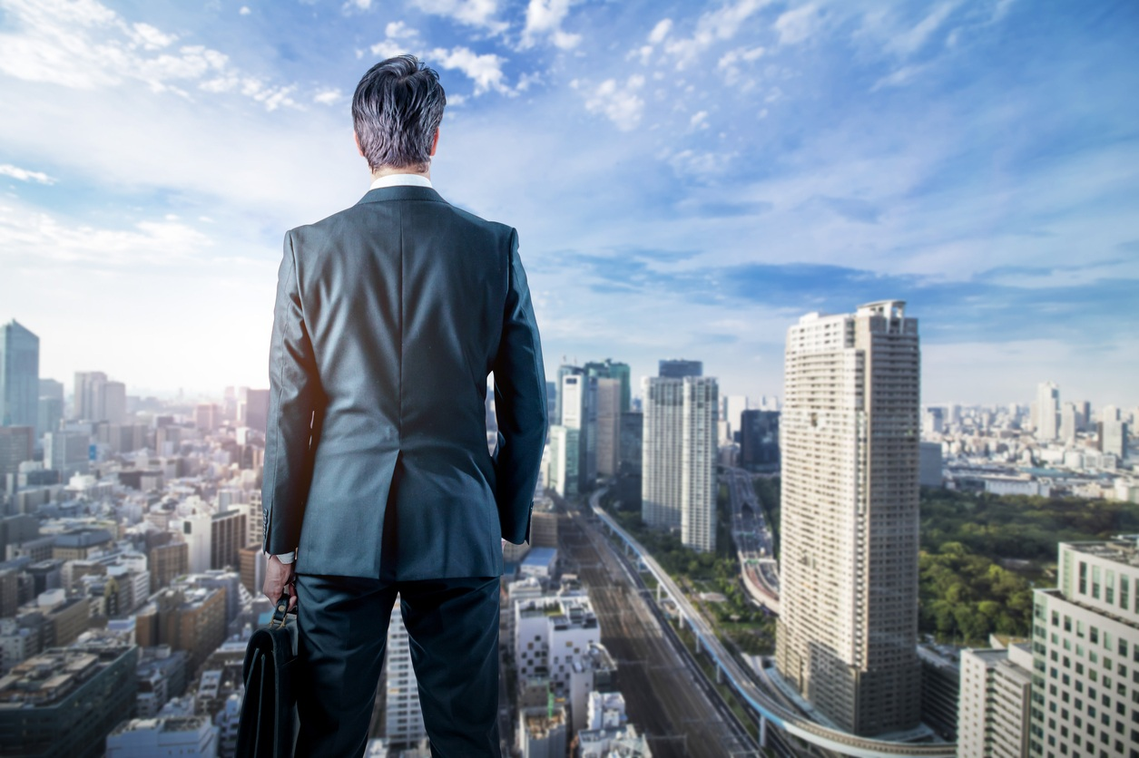 Businessman-looking-down-a-modern-city.-business-prospect-concept.jpg