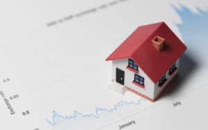 Miniature House on A Blue Financial Graph