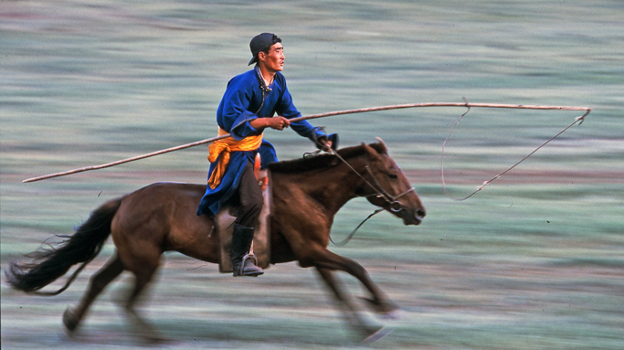 A nomad riding on horseback in Mongolia