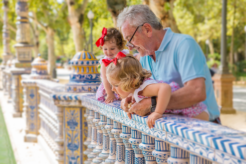 Grandfather playing with two young girls at Plaza de España in Seville, Spain. Travel documents for grandkids