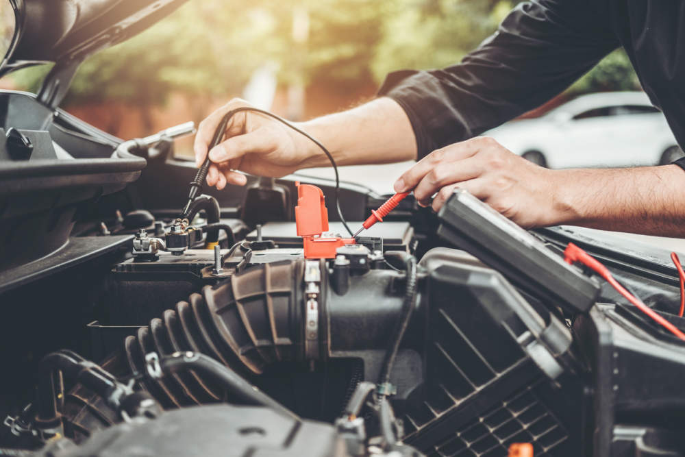 Qualified mechanic testing car battery