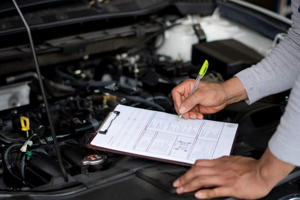 Mechanic conducting a log book service on a car.