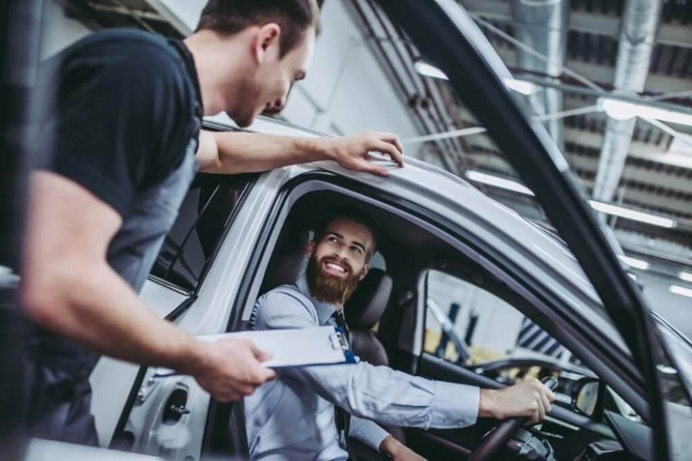 Mechanic discussing car service with a happy customer.