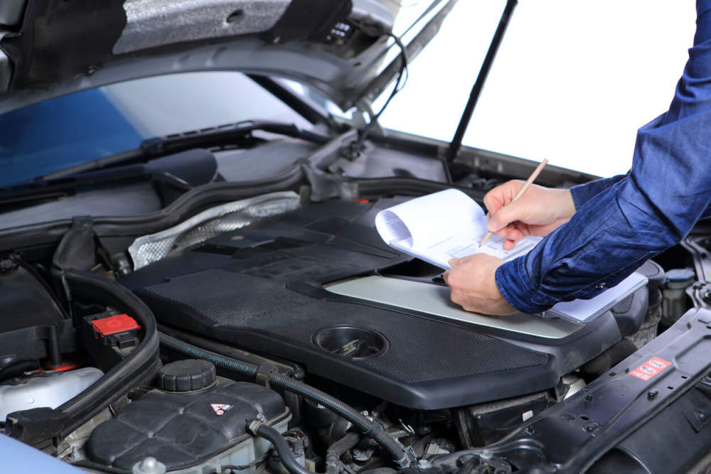 Mechanic completing checks for a car service.