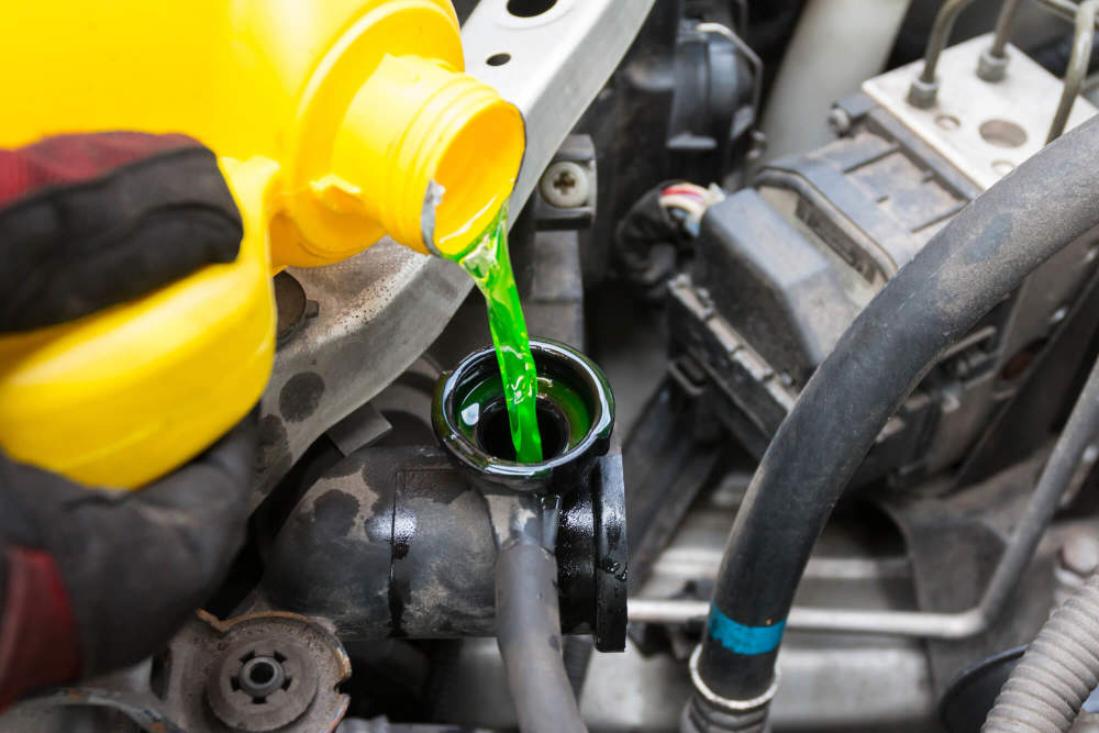 Mechanic pouring coolant into a car radiator.