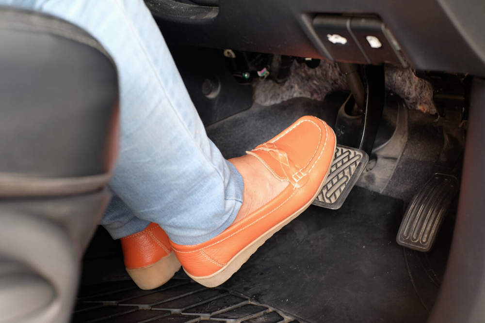 Driver's foot on car brake pedal.