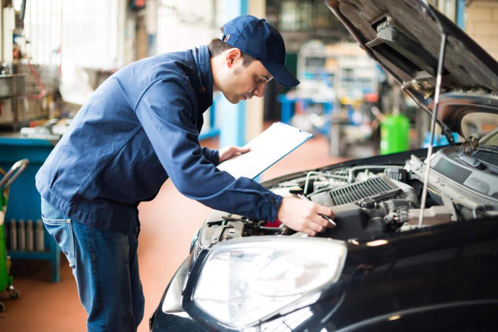 Technician assessing car air filter.
