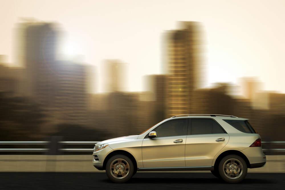 Luxury SUV driving through city landscape.