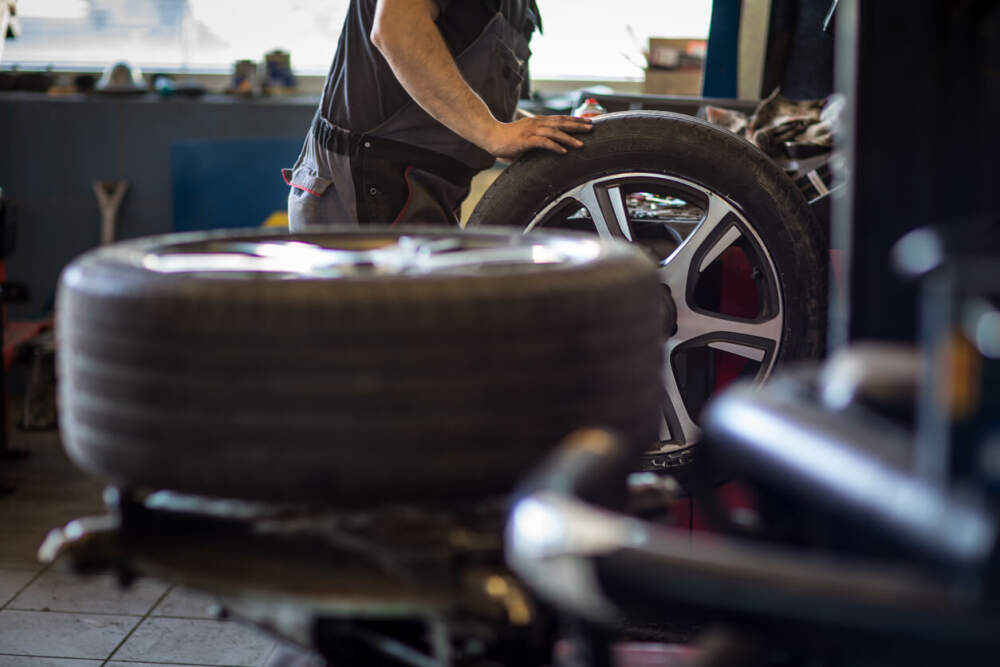 Technician working with a set of new car tyres.