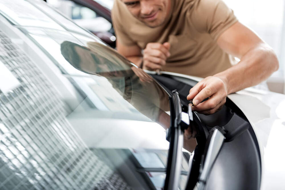 Person inspecting the condition of the wiper blades on a passenger car.