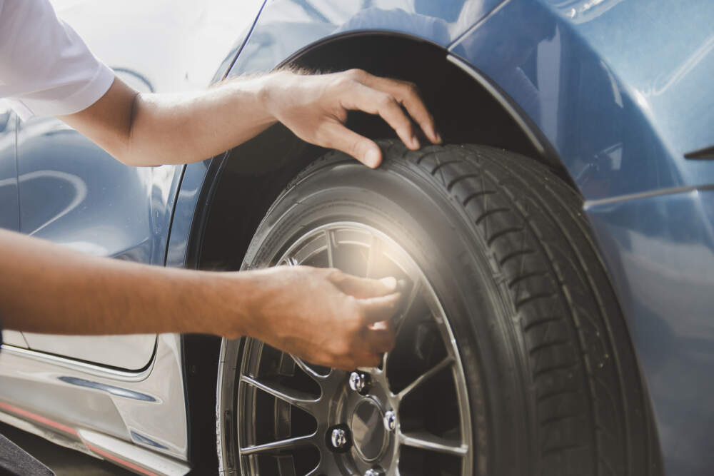 Person assessing the condition of a car tyre.