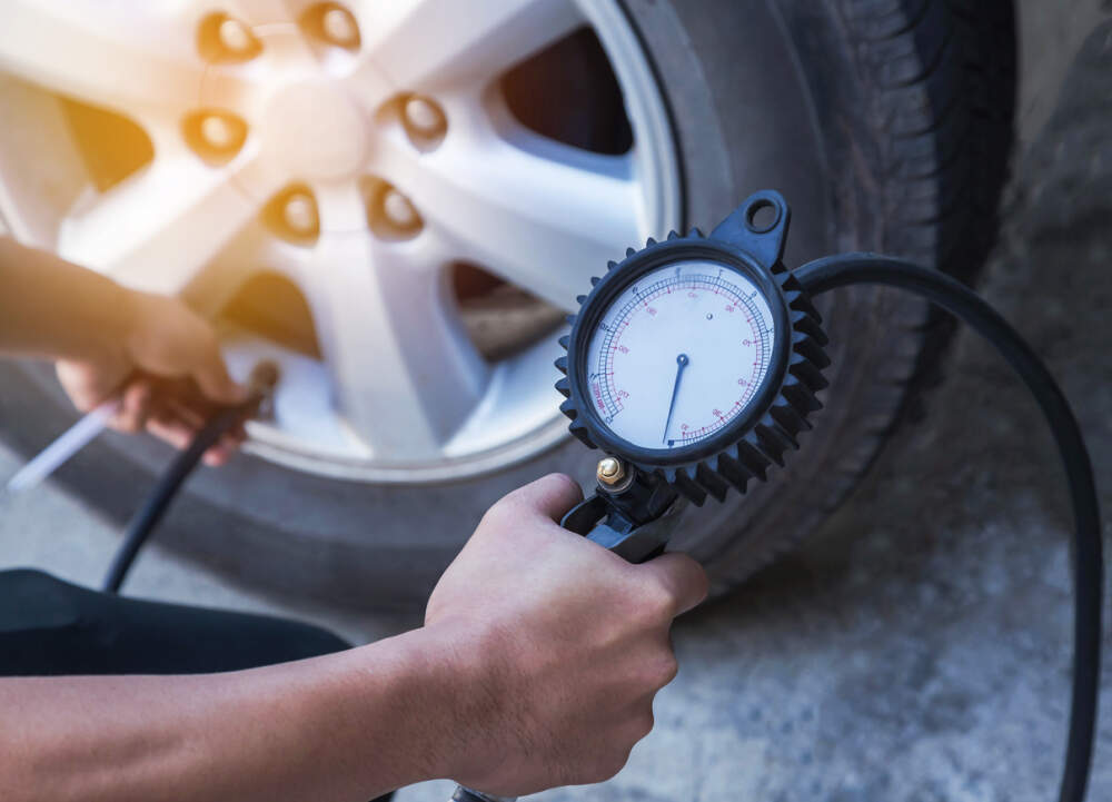 Checking car tyre pressure.