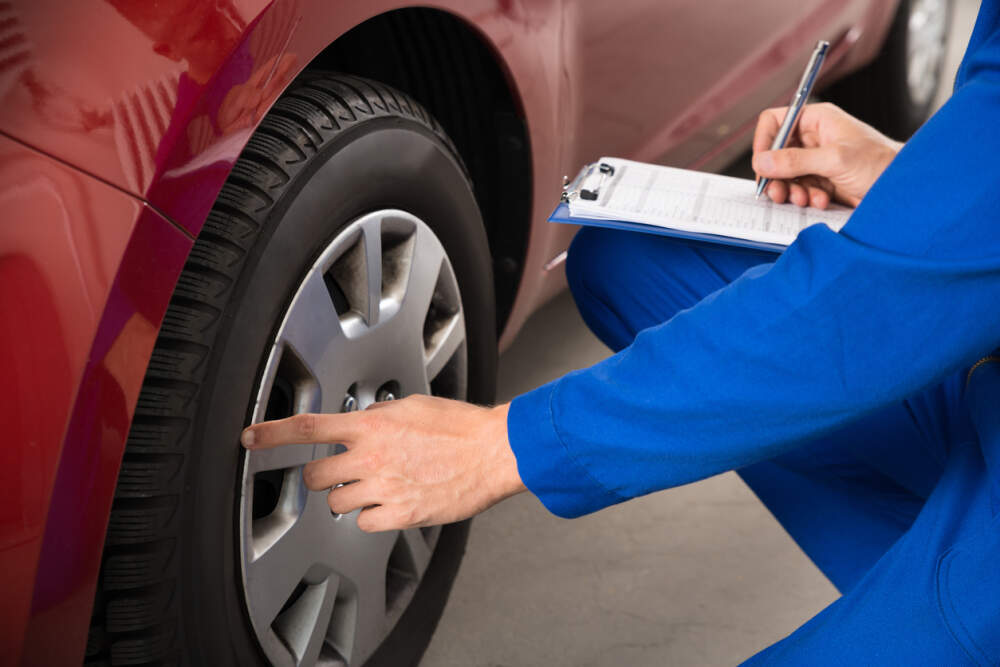 Technician assessing the condition of a car tyre.