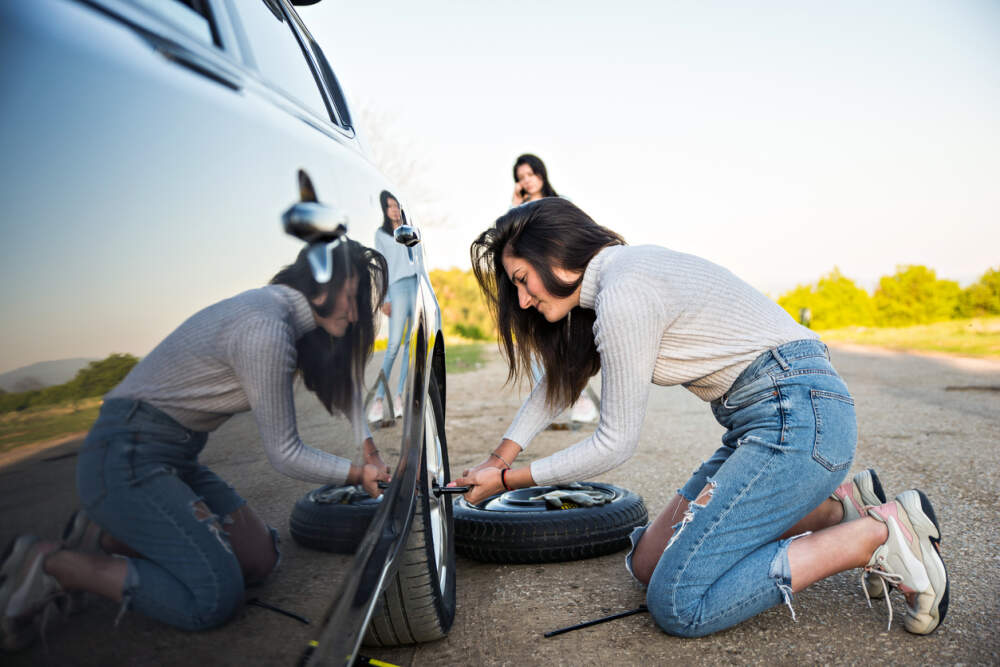 Person changing a flat tyre on a car.