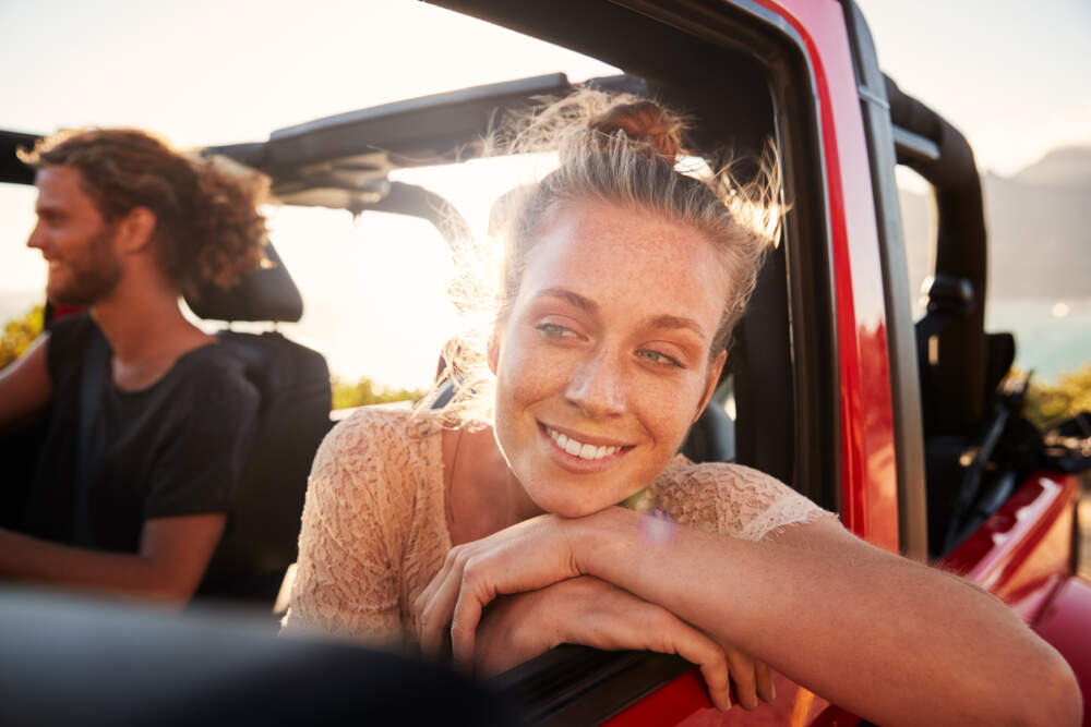 A young couple driving in their car during summer.
