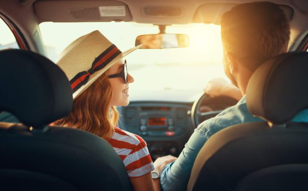 Young couple travelling in their car on a sunny day.