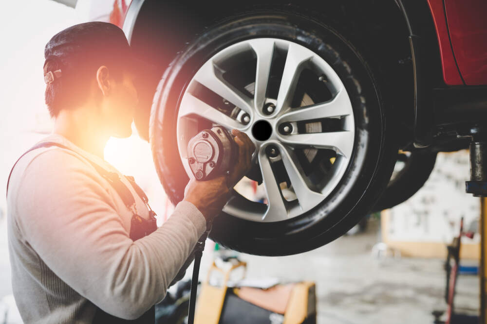 Mechanic fitting new tyres to a car.