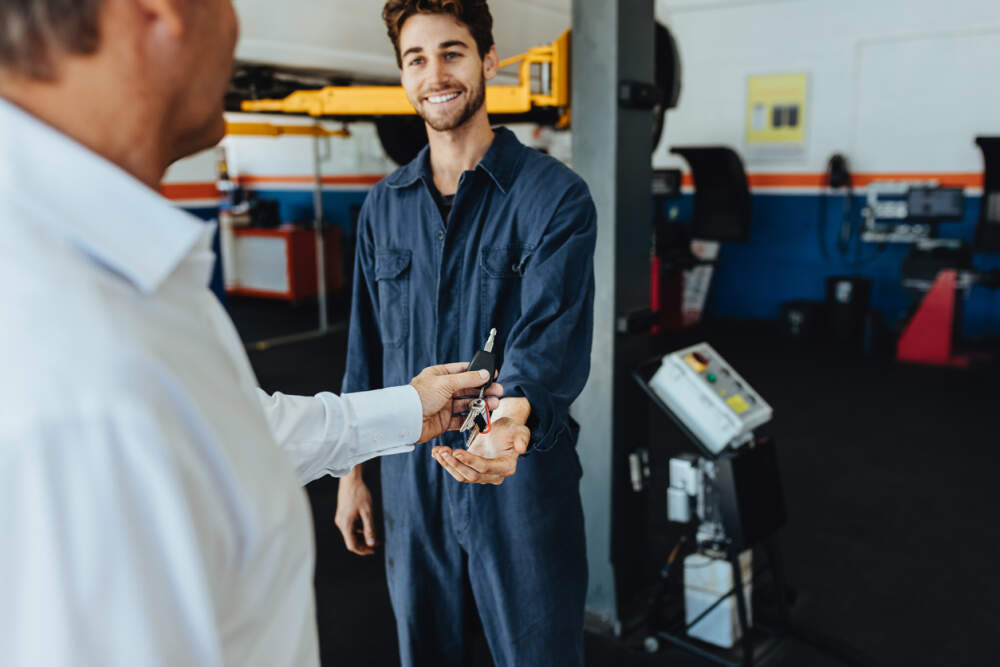 Mechanic and a customer exchanging car keys in a workshop.