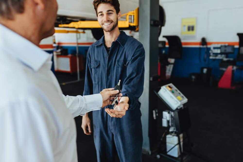 Customer handing over their car keys to a technician in a car workshop.