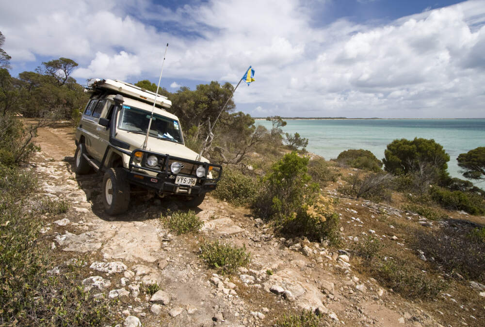 4WD vehicle driving over rocky terrain.
