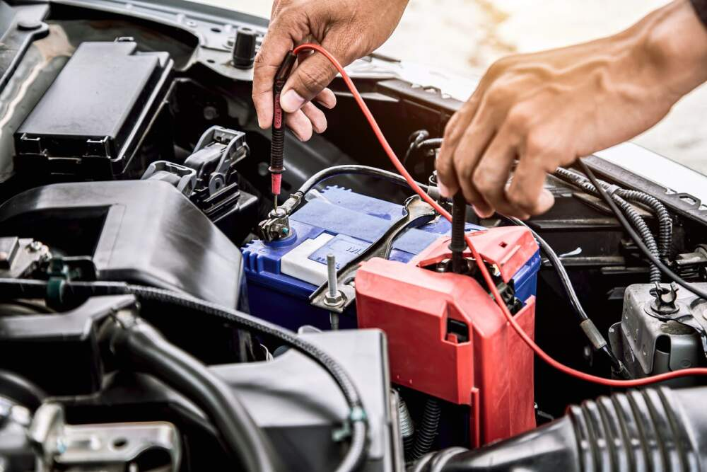 Person testing the condition of a car battery.