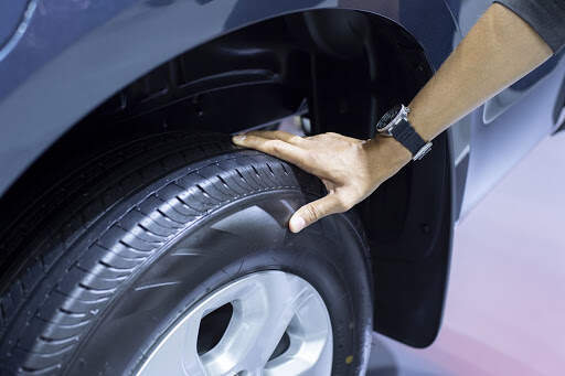 Person assessing the age of a car tyre.